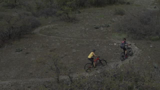 aerial view of people riding mountain bikes on winding trail / cedar hills, utah, united states - 曲線点の映像素材/bロール