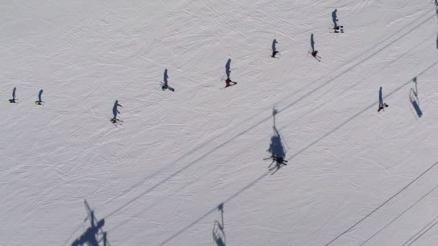 Aerial view of people skiing by ski lift
