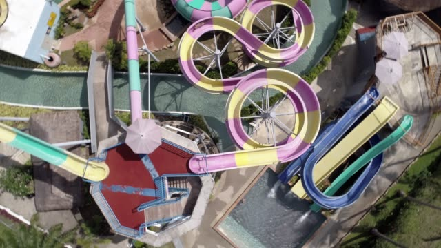 aerial view of people sliding down a water slide at a water park - water slide stock videos & royalty-free footage