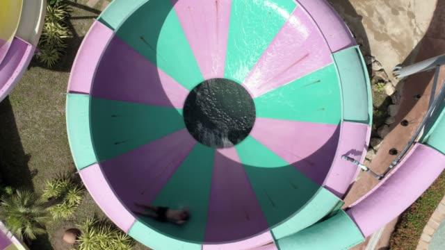 luftaufnahme des menschen rutschen wasserrutsche in einem wasserpark - wasserrutsche stock-videos und b-roll-filmmaterial