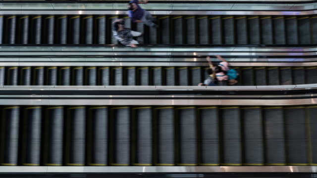 vídeos de stock, filmes e b-roll de aerial view of people using escalators inside ciputra world shopping mall - degraus