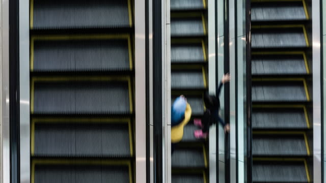 vidéos et rushes de aerial view of people using escalators inside ciputra world shopping mall - se déplacer vers le bas