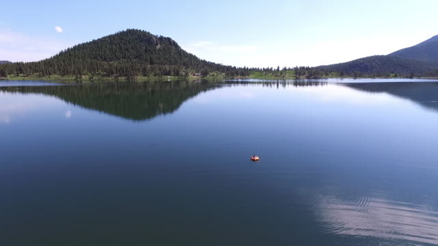 aerial view of person relaxing on float over lake against sky, drone approaching slowly towards woman enjoying weekend at tranquil location - lake wellington, colorado - auf dem wasser treiben stock-videos und b-roll-filmmaterial