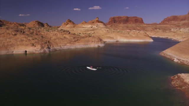 aerial view of person rocking on paddleboard in lake / lake powell, arizona, united states - lake powell stock videos and b-roll footage
