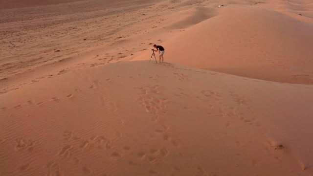 Aerial view of photographer on top of dunes in desert at sunset