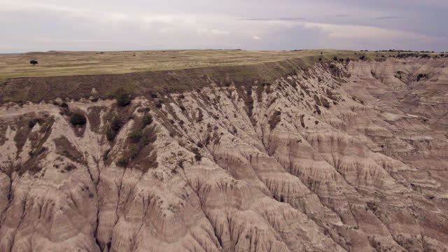 DRONE. Aerial view of prehistoric Badlands canyons below a grassy plateau field