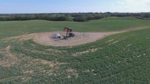 vídeos de stock, filmes e b-roll de aerial view of pumpjack in a farmers field - movimento perpétuo