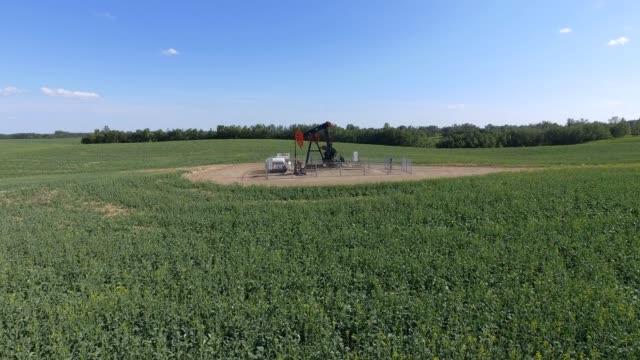 aerial view of pumpjack in a farmers field - pump jack stock videos & royalty-free footage