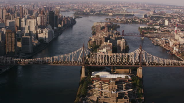 aerial view of queensboro bridge and roosevelt island flying over east river, nyc - queensboro bridge stock videos & royalty-free footage