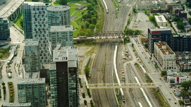 aerial view of  railway tracks with trains passing under sir isaac brock bridge with traffic between high rise buildings -wide shot - spoonfilm stock-videos und b-roll-filmmaterial