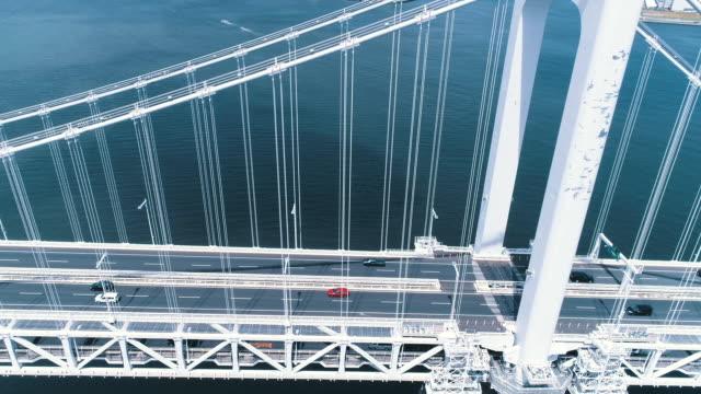 aerial view of rainbow bridge crossing over the sea - 陸上交通工具 個影片檔及 b 捲影像