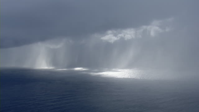 aerial view of rainstorm over the pacific ocean near the eastern coast of molokai, hawaii. - coastal feature stock videos & royalty-free footage