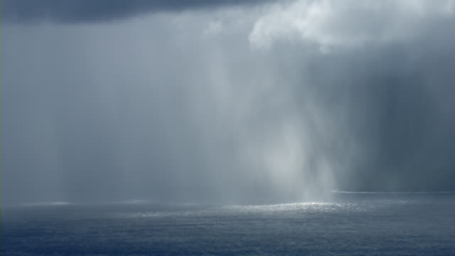 Aerial view of rainstorm with sunbeams shining through dense clouds off the Eastern coast of Molokai, Hawaii.