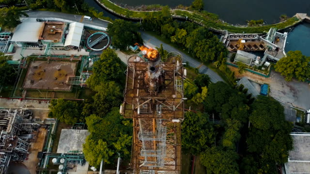aerial view of refinery plant with burning torch - fuel crisis stock videos and b-roll footage