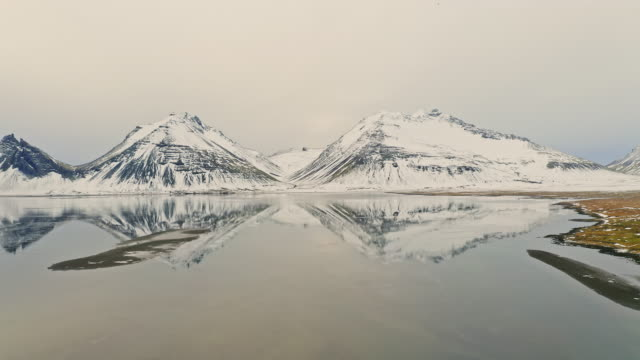 aerial view of reflection of mountains in iceland next to the sea at winter - wilderness stock videos & royalty-free footage