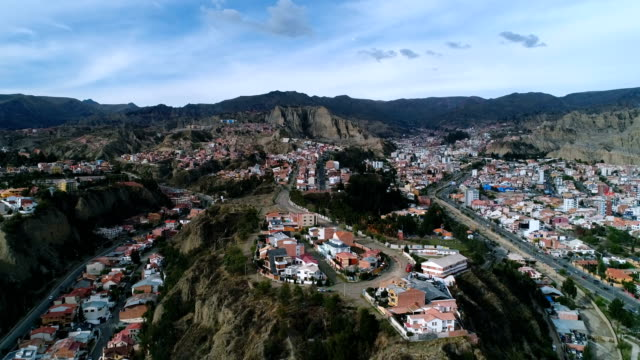 aerial view of residential district and rocky mountain range in la paz - ボリビア点の映像素材/bロール