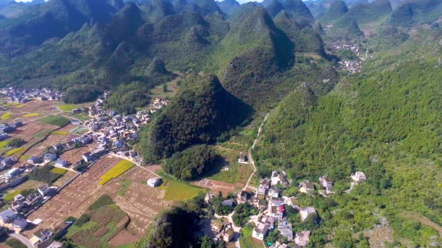 Aerial view of Rice Paddy and Traditional Chinese Green Village in Valley, Yunnan Province, China