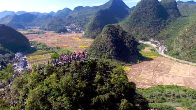 aerial view of rice paddy and traditional chinese green village in valley, yunnan province, china - yunnan province stock videos and b-roll footage