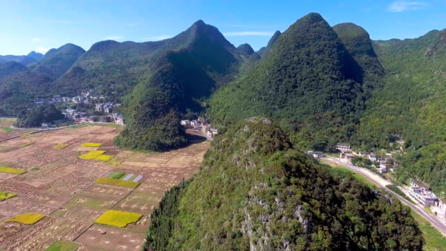 Aerial view of Rice Paddy and Traditional Chinese Village in Green Valley, Yunnan Province, China