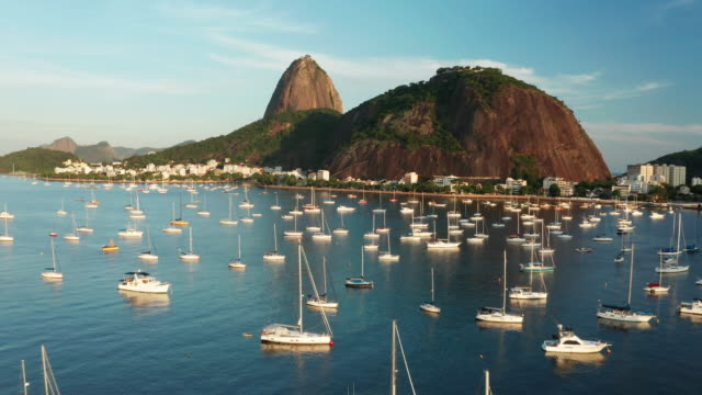 aerial view of rio de janeiro at susnet, brazil. sugarloaf mountain and botafogo bay. - naturligt landmärke bildbanksvideor och videomaterial från bakom kulisserna
