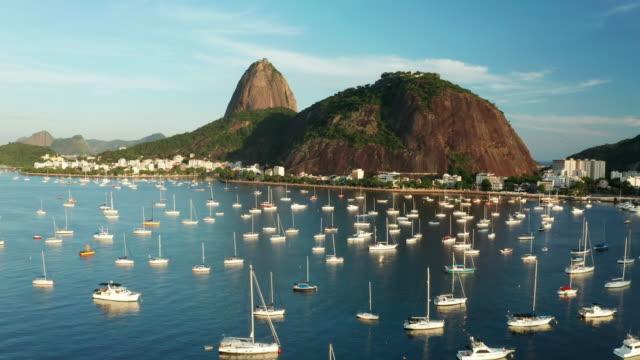 vídeos de stock e filmes b-roll de aerial view of rio de janeiro at susnet, brazil. sugarloaf mountain and botafogo bay. - copacabana