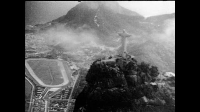vídeos de stock, filmes e b-roll de / aerial view of rio de janerio / christ the redeemer statue on top of hill with mist all around / above the cityscape landscape of brazil on january... - 1940
