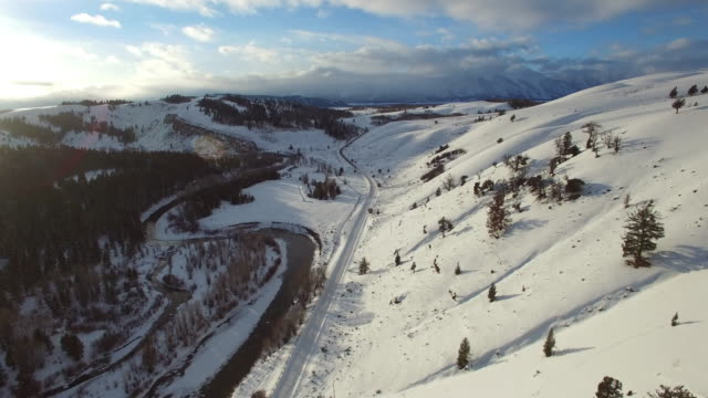 aerial view of river amidst snow covered road and evergreen trees, scenic view of white mountains against sky during sunset - jackson, wyoming - wyoming bildbanksvideor och videomaterial från bakom kulisserna