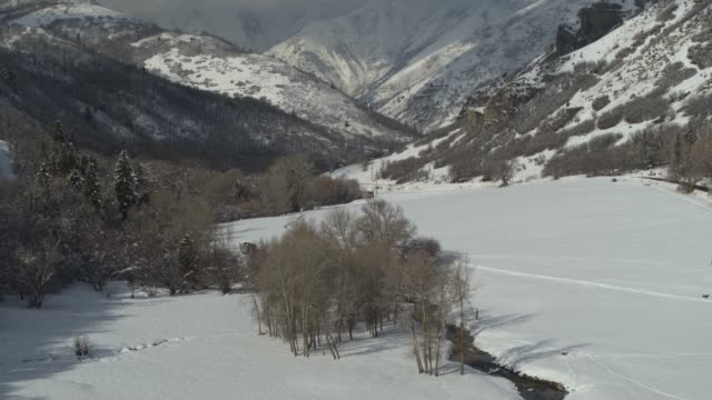 aerial view of river approaching mountain range in winter / south fork, utah, united states - cold temperature stock videos & royalty-free footage