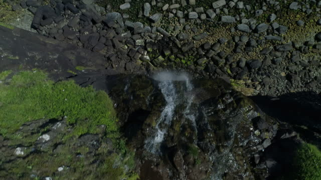 aerial view of river as water flows towards the edge of a cliff creating a beautiful waterfall - hebrides stock videos & royalty-free footage
