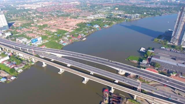 vídeos y material grabado en eventos de stock de vista aérea del puente sobre el río y el tráfico en la zona suburbana en bangkok - tren elevado