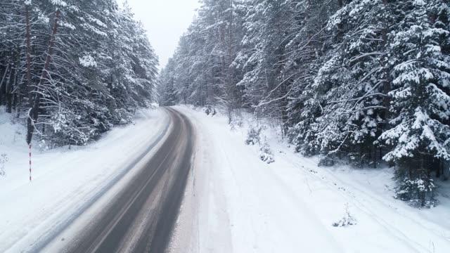 luftaufnahme der straße im winter. auto fährt auf der straße - aircraft point of view stock-videos und b-roll-filmmaterial