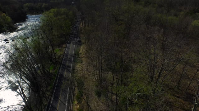 aerial view of road running parallel to river, moving over trees along the bank - contea di ulster stato di new york video stock e b–roll