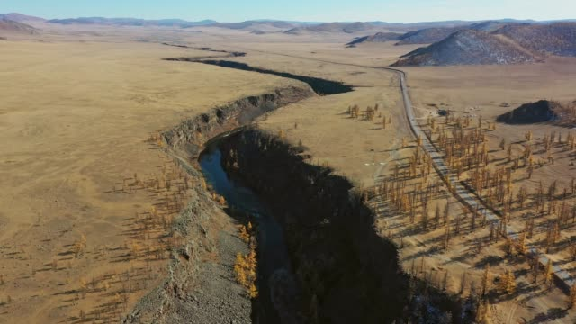 aerial view of road through steppe at sunset - steppe stock videos & royalty-free footage