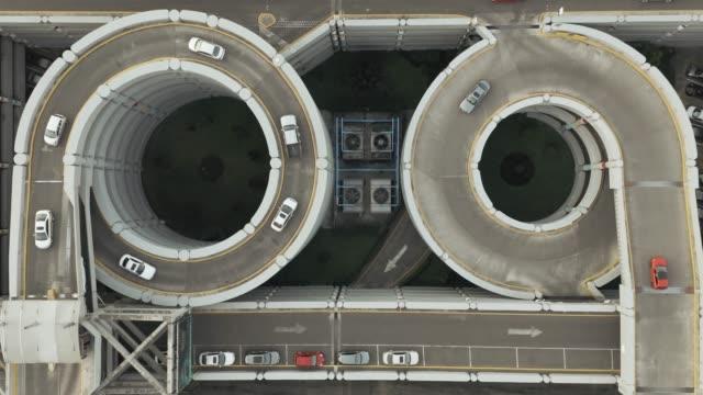 vídeos de stock e filmes b-roll de aerial view of road with carpark entrance - estacionamento de carros