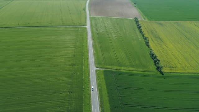 aerial view of road with driving car in rural landscape with agricultural fields. franconia, bavaria, germany, europe. - blickwinkel der aufnahme stock-videos und b-roll-filmmaterial