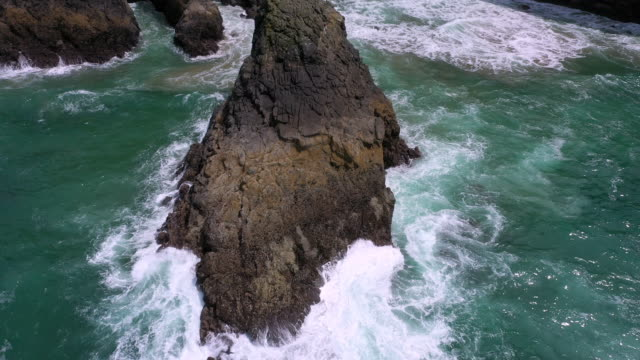 aerial view of rock as waves crash into it - oregon coast stock videos & royalty-free footage
