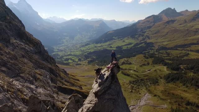 vídeos y material grabado en eventos de stock de aerial (drone) view of rock climbers ascending cliff - escala