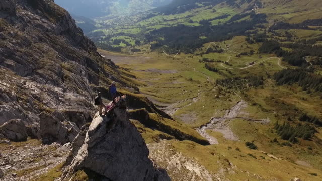 aerial (drone) view of rock climbers looking off cliff - oben stock-videos und b-roll-filmmaterial