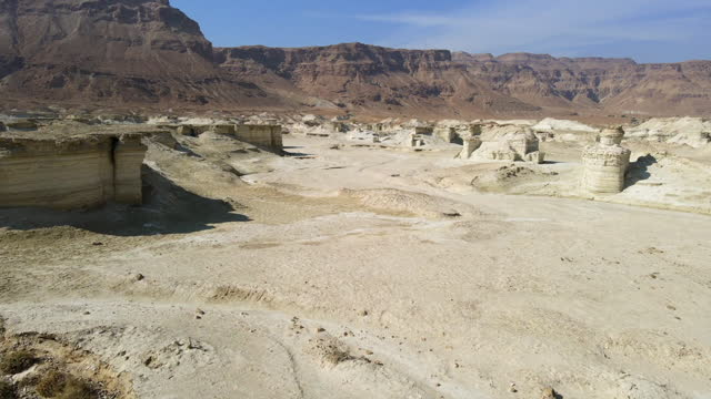aerial view of rock formations against cliff at masada national park on sunny day, drone flying forward over landscape - öde landschaft stock-videos und b-roll-filmmaterial
