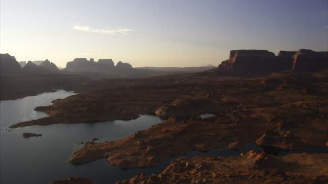 aerial view of rock formations and lake at sunset / lake powell, arizona, united states - lake powell stock videos and b-roll footage