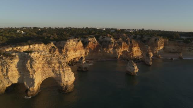 vídeos y material grabado en eventos de stock de aerial view of rock formations at ocean cove / praia de marinha, faro, portugal - acantilado