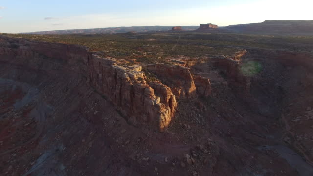 aerial view of rocky mountain in desert against sky, drone moving forward towards cliff on barren landscape - moab, utah - moab utah stock videos & royalty-free footage