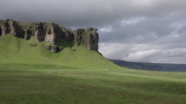 aerial view of rocky mountain on beautiful green landscape, drone flying forwards while ascending towards cloudy sky - southwestern iceland, iceland - hay isolated stock videos & royalty-free footage