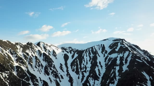 aerial view of rocky snow-covered mountain peak - clear sky stock videos & royalty-free footage