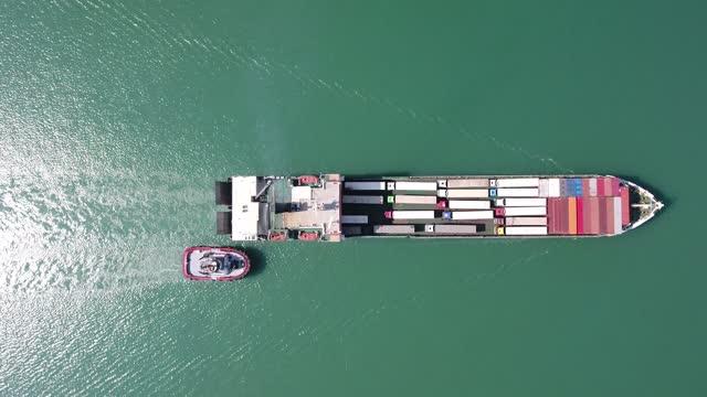 vidéos et rushes de vue aérienne d'un navire roulier s'approchant d'un port commercial. - montrer la voie