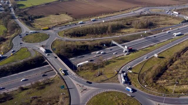 vídeos y material grabado en eventos de stock de aerial view of roundabout adjacent to the m1 motorway. locked off. - export palabra en inglés