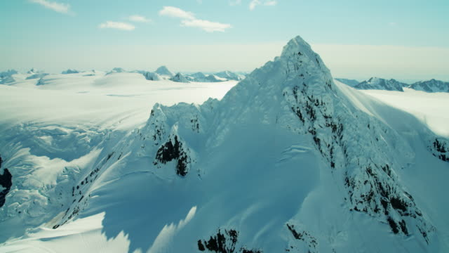 vídeos de stock, filmes e b-roll de aerial view of rugged snow covered mountains alaska - eco tourism