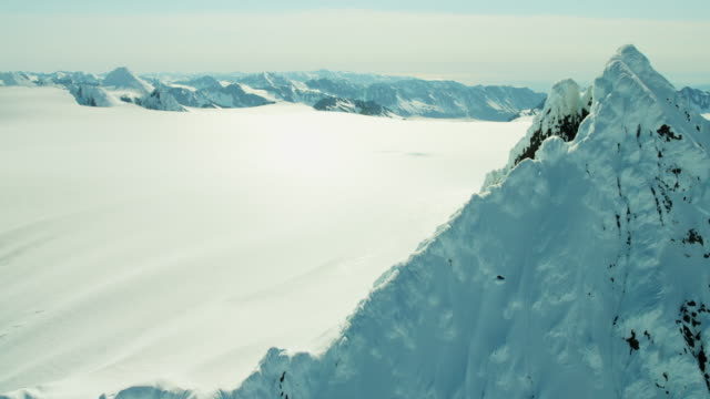 stockvideo's en b-roll-footage met aerial view of rugged snow covered mountains alaska - arctis