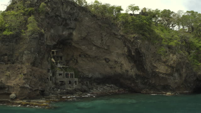 aerial view of ruins in rock formation cave near ocean / moonhole, bequia, saint vincent and the grenadines - 沿岸点の映像素材/bロール