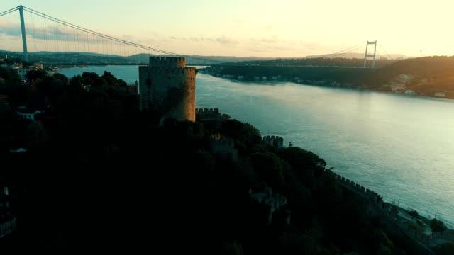vídeos de stock, filmes e b-roll de vista aérea da fortaleza e da ponte de rumeli no bósforo de istambul no nascer do sol - turquia